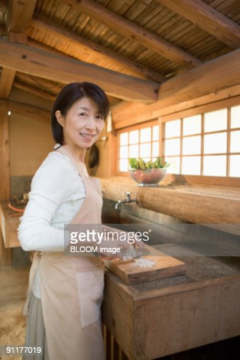Mature woman cooking in traditional japanese kitchen for Traditional japanese kitchen