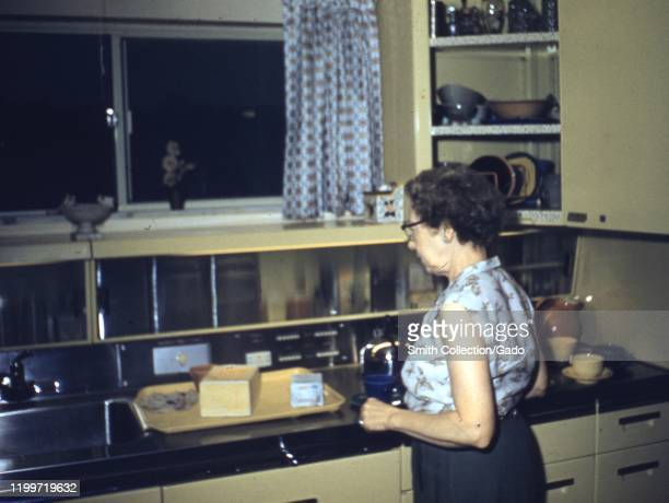 A mature woman cooks in a domestic kitchen 1959