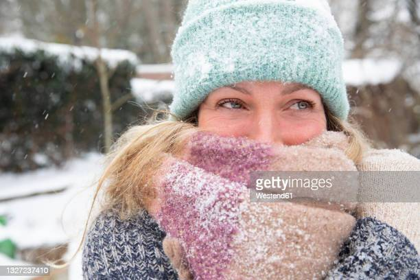 mature woman covering face with scarf during winter looking away - glove stock pictures, royalty-free photos & images