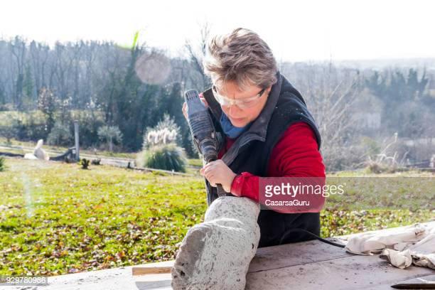 Mature Woman  Creating Stone Sculpture