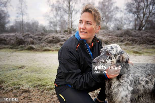 mature woman crouching down stroking dog looking away - bush dog stock pictures, royalty-free photos & images