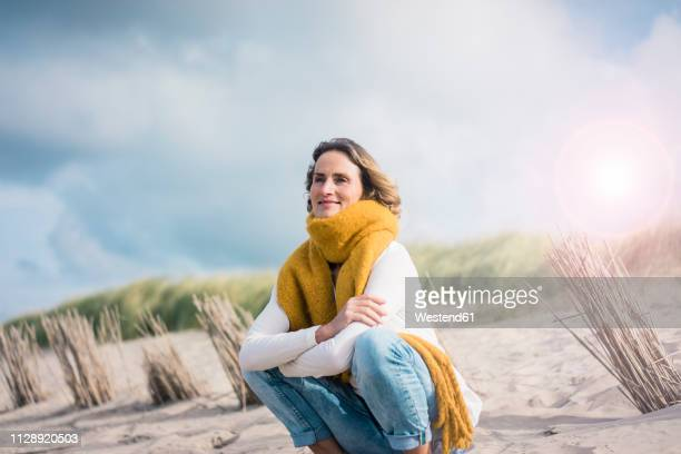 mature woman crouching in the dunes, enjoying the wind - マフラー ストックフォトと画像