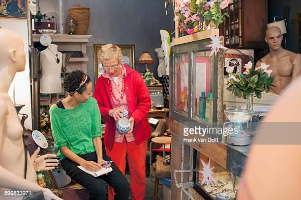 Mature woman customer examining china pot in vintage shop