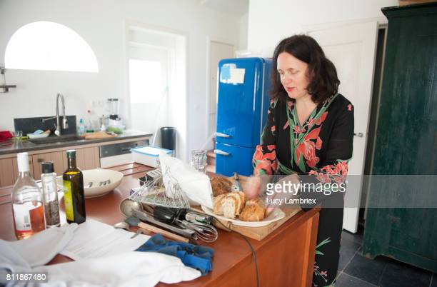 Mature woman cutting bread in the kitchen