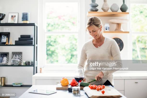 mature woman cutting fresh vegetables in kitchen - chop stock pictures, royalty-free photos & images