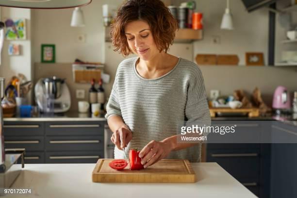 mature woman cutting tomato in kitchen - einfaches leben stock-fotos und bilder