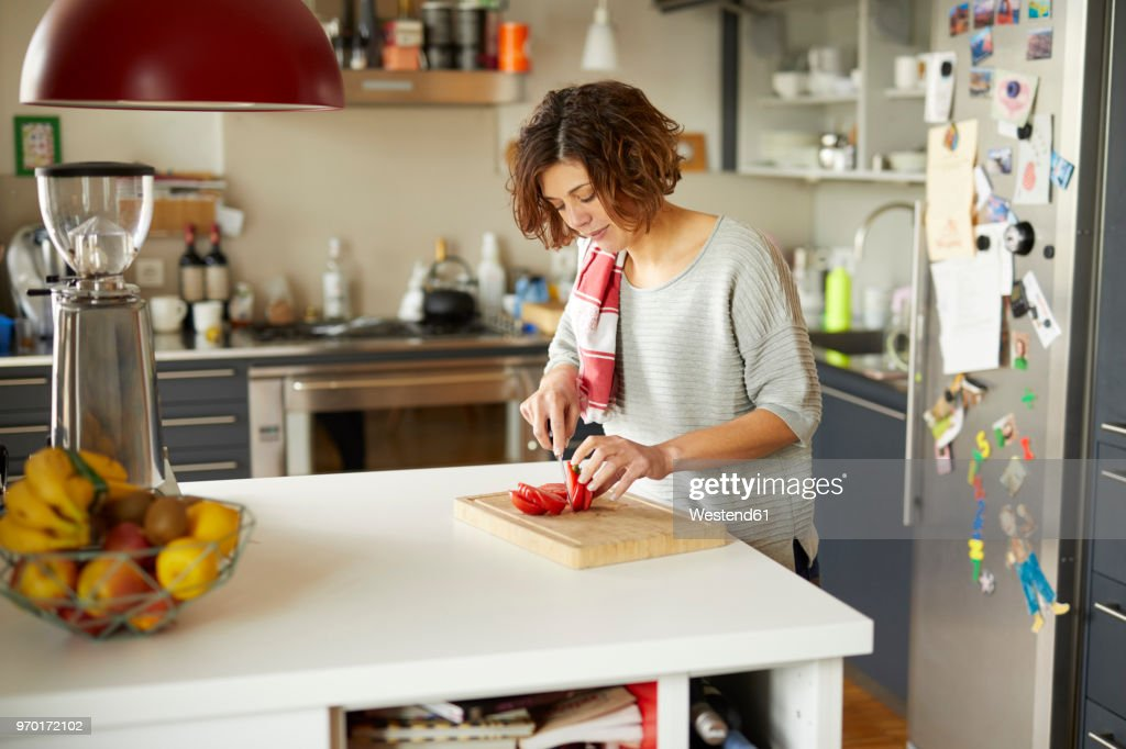 Mature woman cutting tomato in kitchen : Stock Photo