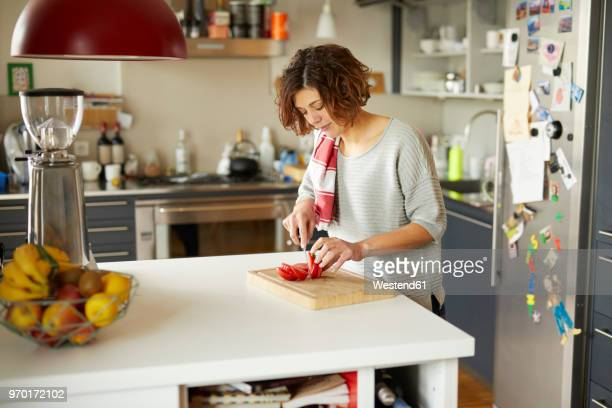 mature woman cutting tomato in kitchen - dish towel stock pictures, royalty-free photos & images