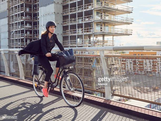 Mature woman cycling on footbridge against building