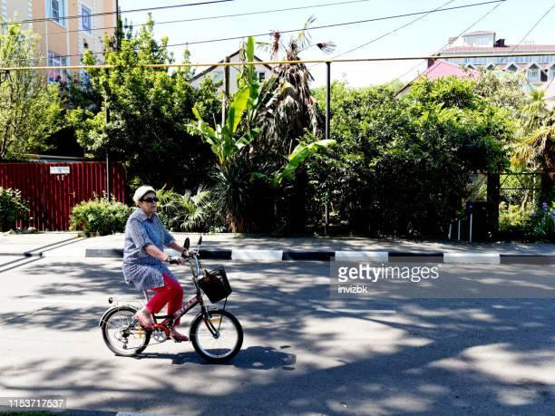 madura mujer ciclismo - human powered vehicle fotografías e imágenes de stock