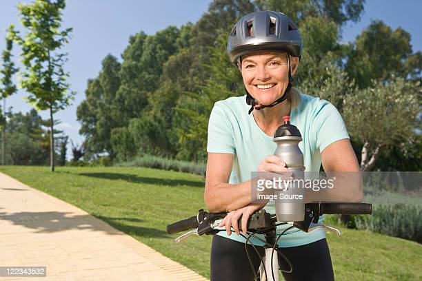 mature woman cyclist wearing helmet and holding bottle - cycling helmet stock photos and pictures