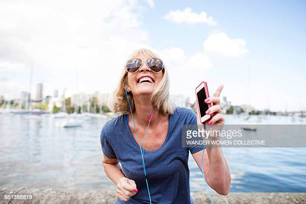 mature woman dancing to mpg with earphone - listening stock pictures, royalty-free photos & images