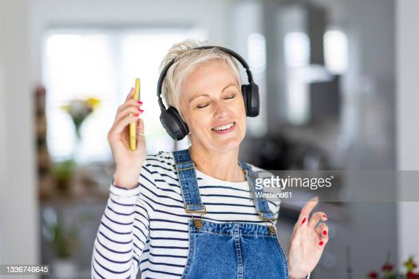 mature woman dancing while listening music at home - listening stock pictures, royalty-free photos & images