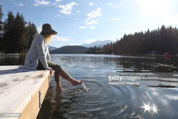 mature woman dangles feet in a mountain lake at sunrise - simple living stock pictures, royalty-free photos & images