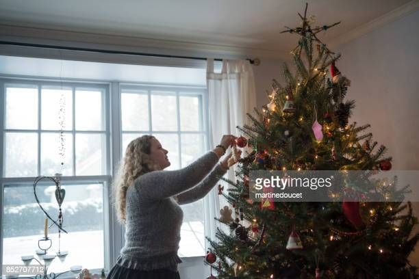 Mature woman decorating Christmas tree at home.