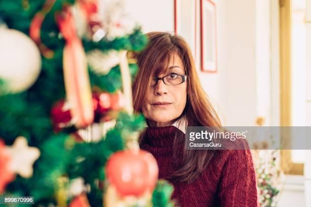 Mature Woman Decorating Christmas Tree