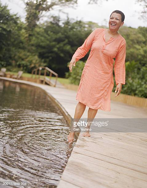 mature woman dipping toe in pool, laughing - 人のつま先 ストックフォトと画像