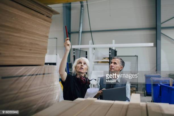 mature woman discussing with colleague while examining wooden planks at industry - lumber industry stock pictures, royalty-free photos & images