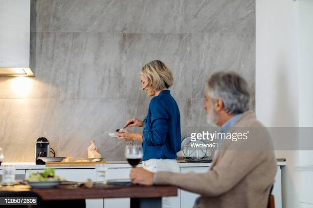 mature woman dishing up dinner in kitchen at home - 妻 ストックフォトと画像