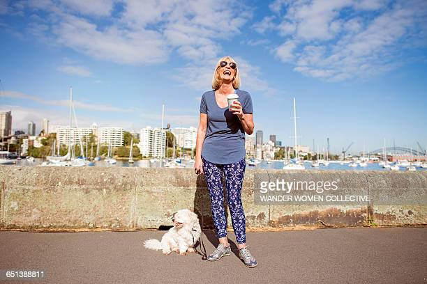 Mature woman dog laughing with take away coffee