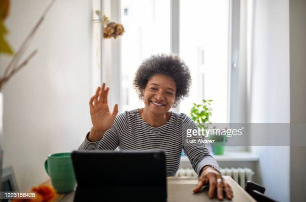 mature woman doing a video call during home quarantine - women stock pictures, royalty-free photos & images