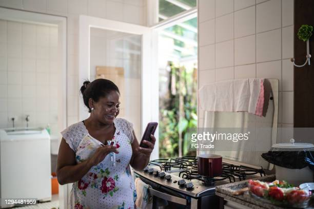 mature woman doing a video call on smartphone at home - candid forum stock pictures, royalty-free photos & images