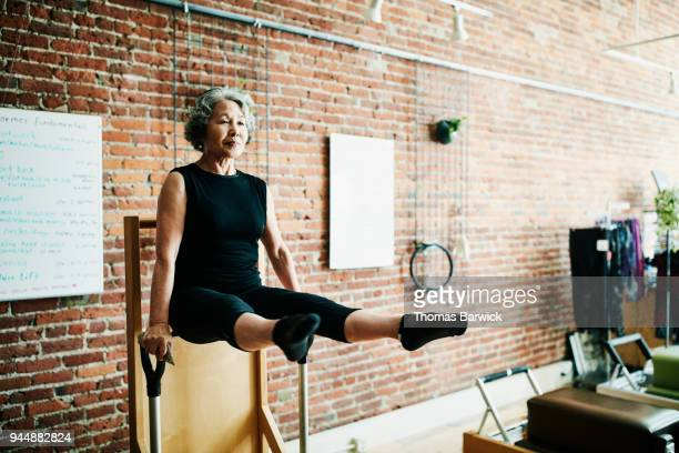 Mature woman doing arm press on high-low pilates chair in fitness studio