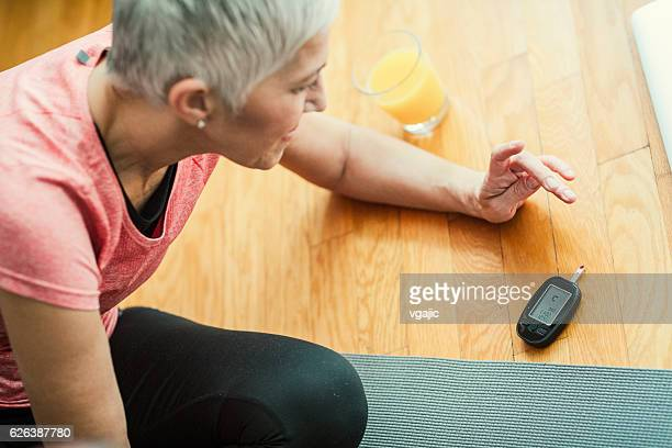 mature woman doing blood sugar test after exercise. - diabetes stock pictures, royalty-free photos & images