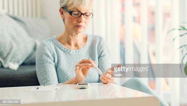 Mature Woman Doing Blood Sugar Test at home.