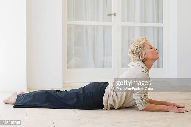 mature woman doing cobra pose with eyes closed - lying on front stock pictures, royalty-free photos & images
