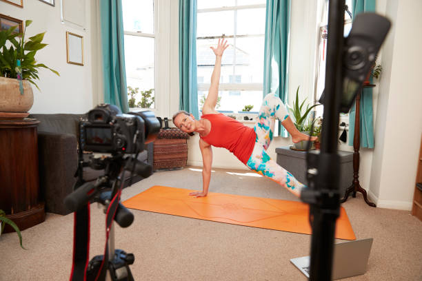 Mature woman doing exercise video recording with camera at home