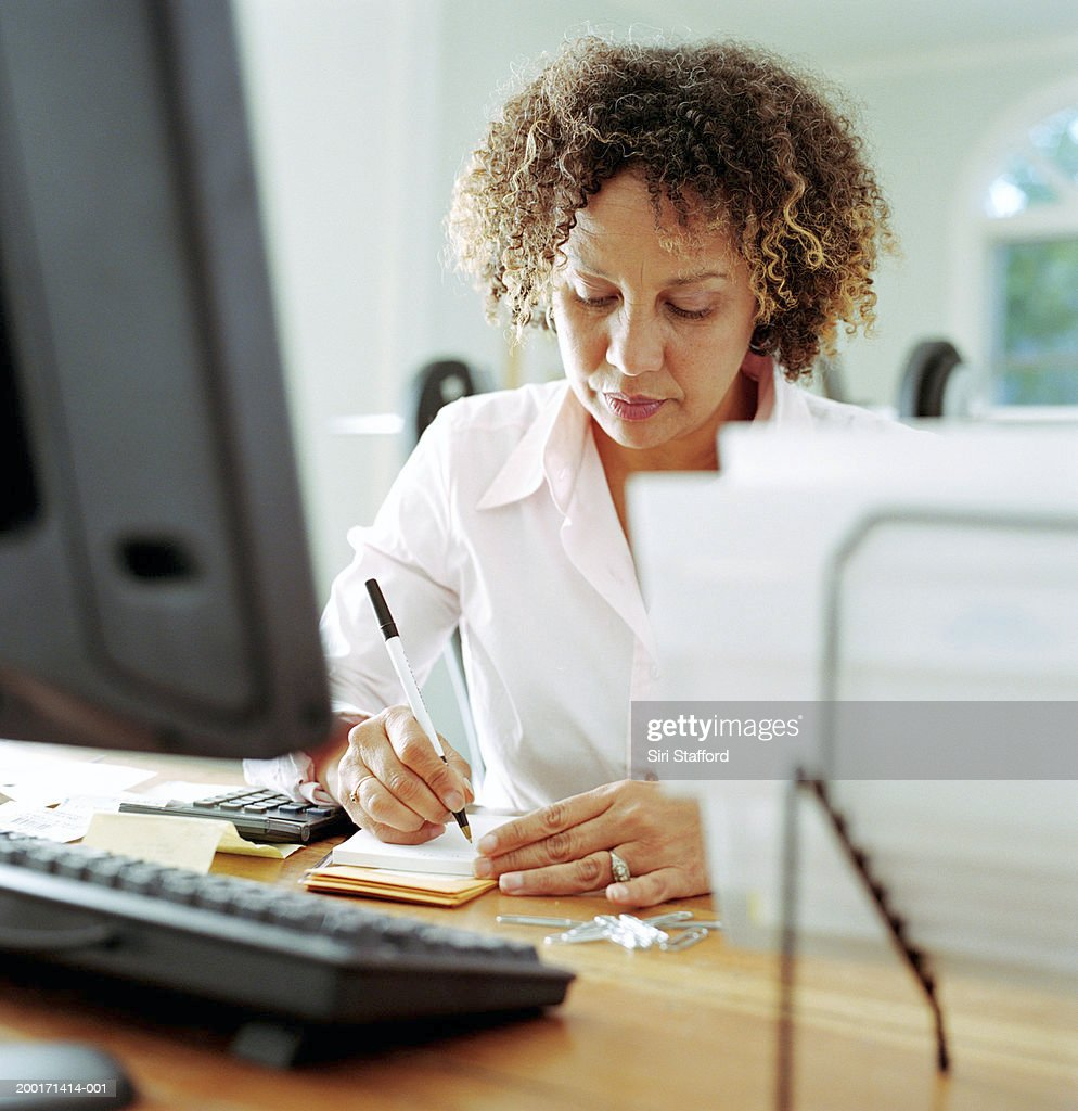 Mature woman doing finances in home office : Stock Photo