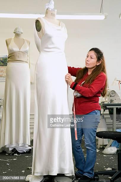 Mature woman doing finishing touches on wedding dress