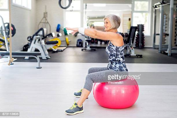 Mature woman doing gymnastics on fitness ball in gym