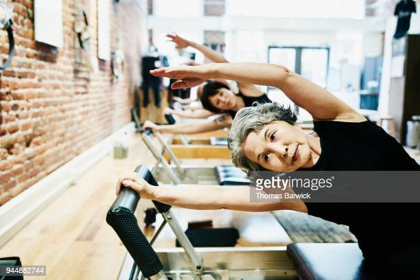 Mature woman doing mermaid exercise on pilates reformer during fitness class in studio