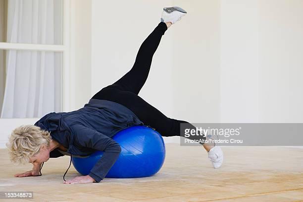 mature woman doing pilates exercise on fitness ball - china foto e immagini stock