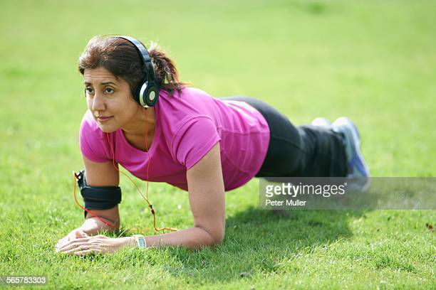 Mature woman doing plank exercises in park