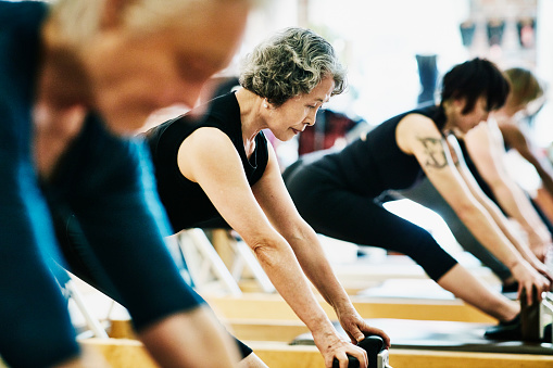 Mature woman doing russian splits on pilates reformer during class in fitness studio - gettyimageskorea