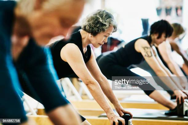 Mature woman doing russian splits on pilates reformer during class in fitness studio