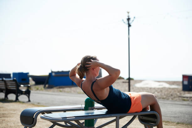 Mature woman doing sit ups on bench during sunny day