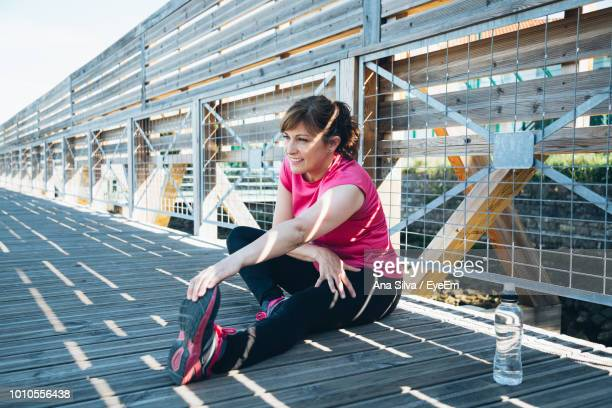 Mature Woman Doing Stretching Exercise On Footbridge