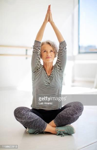 mature woman doing stretching workout - yoga stock-fotos und bilder