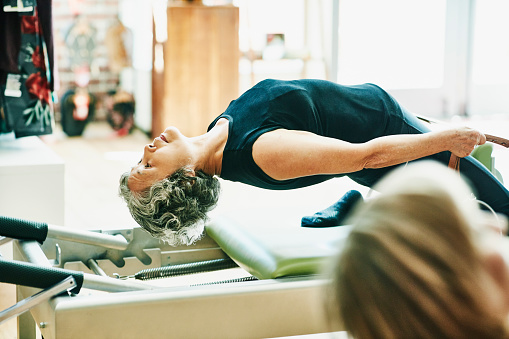 Mature woman doing thigh stretch on pilates reformer during fitness class - gettyimageskorea