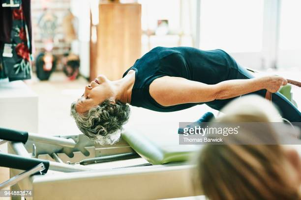 Mature woman doing thigh stretch on pilates reformer during fitness class