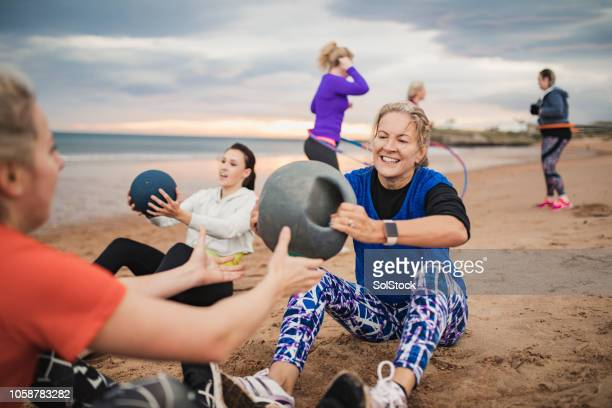 mature woman doing weighted ball exercises - passing sport stock pictures, royalty-free photos & images