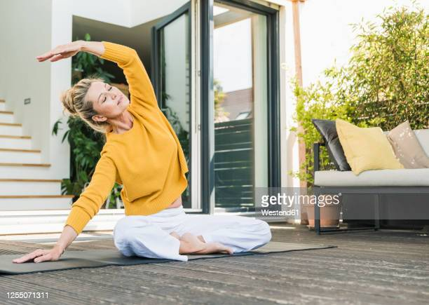 mature woman doing yoga exercise on terrace - beautiful people stock pictures, royalty-free photos & images