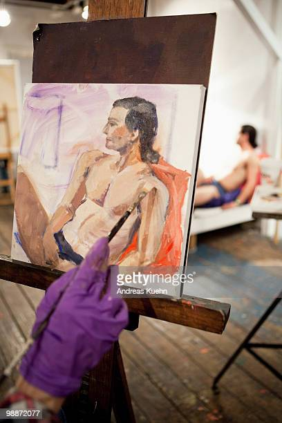 Mature woman drawing picture of nude man.