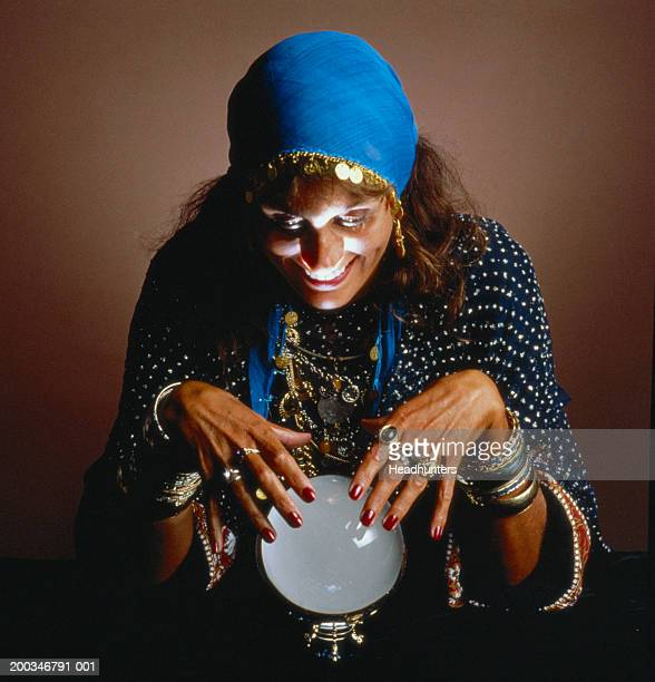 mature woman dressed as gypsy looking into crystal ball - headhunters stock pictures, royalty-free photos & images