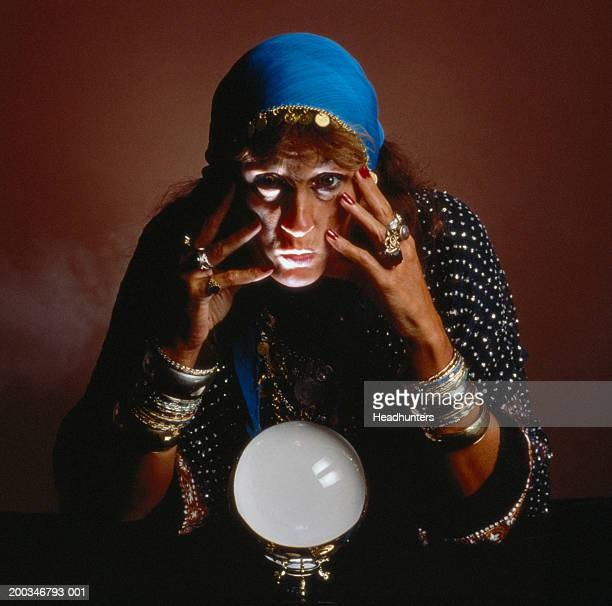 mature woman dressed as gypsy with crystal ball - headhunters stock pictures, royalty-free photos & images