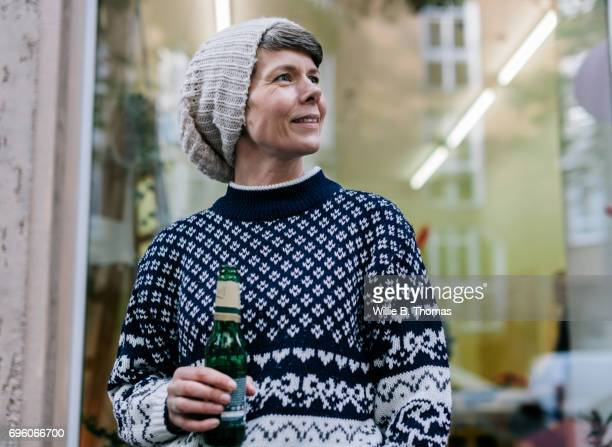 Mature Woman Drinking A Beer Outside A Shop